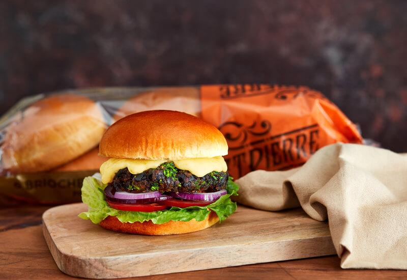 Autumn Burger Recipe Ideas: a vegetarian burger on a wooden board next to a tea towel