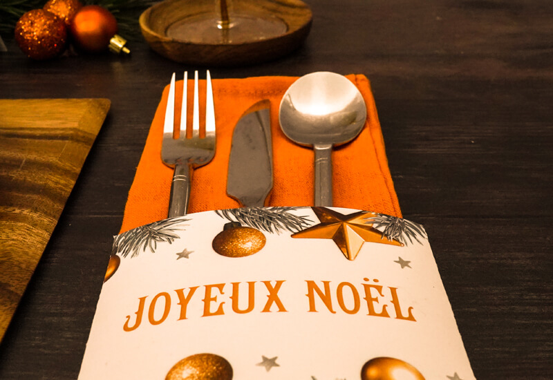 Printable Christmas Decor Kit: a close-up photo of a fork, knife, spoon and orange napkin inside a card napkin and cutlery holder