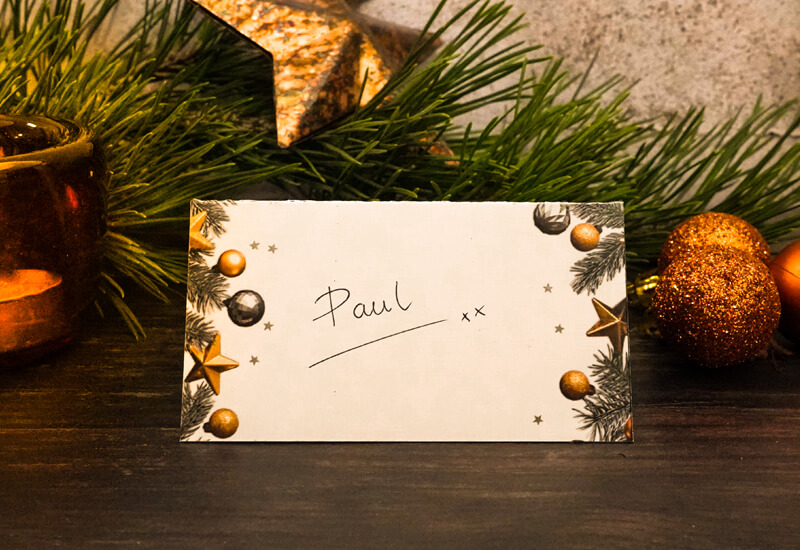 Printable Christmas Decor Kit: a photo of a place card with a Christmas theme and the name Paul written on it