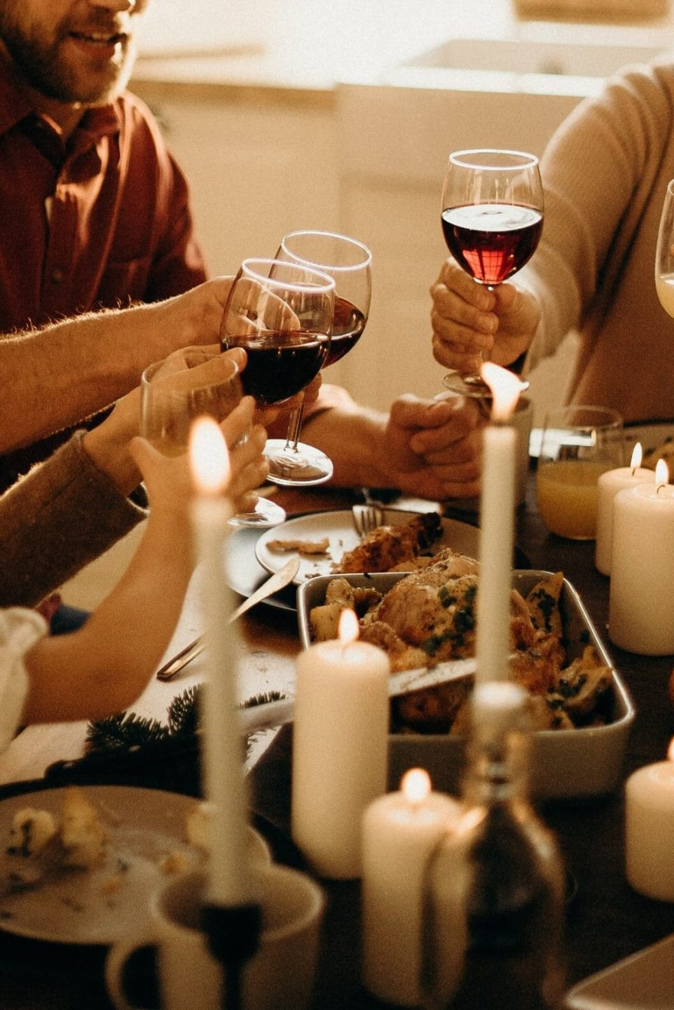 A photo of people sat at a table holding glasses of red wine