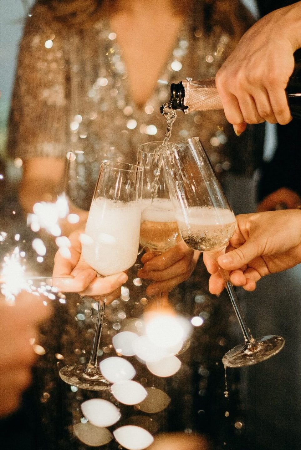 A close-up photo of people holding Champagne flutes