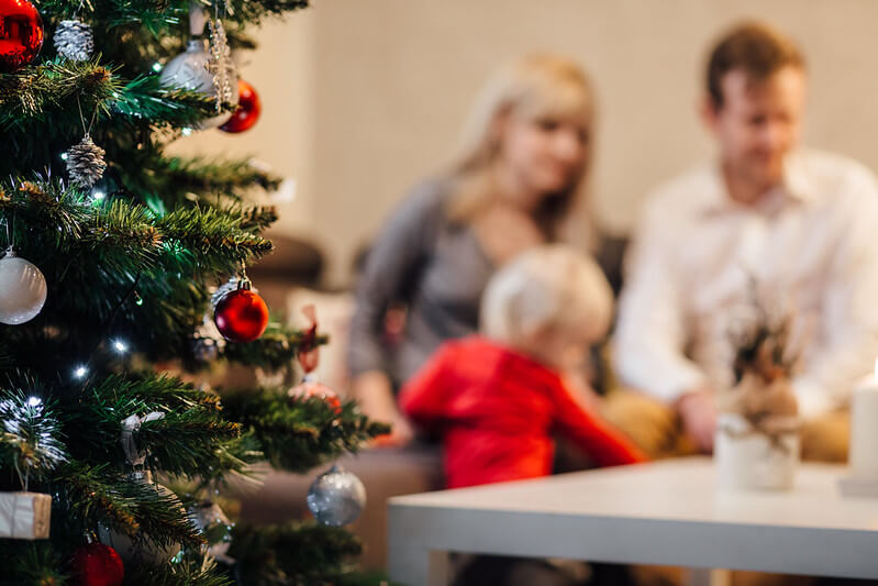 Christmas tips for parents: a photo of a family in the background with a Christmas tree in focus in the foreground