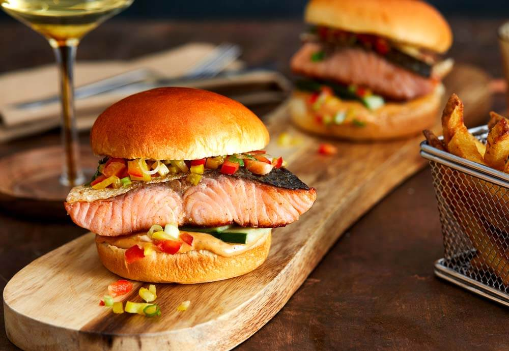 A photo of two burger buns filled with salmon fillets and diced vegetables, on a wooden board