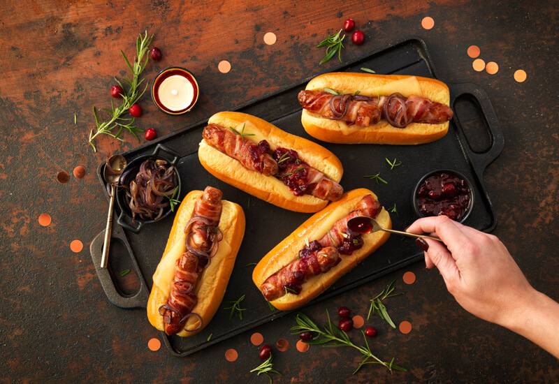 An overhead photo of 'Christmas hot dog rolls with a hand adding cranberry sauce on top