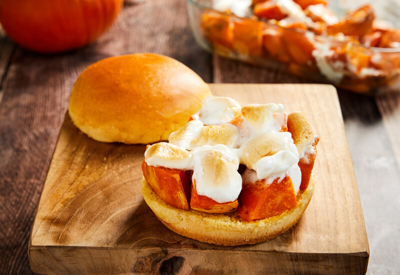 A Brioche burger bun filled with roasted cubed sweet potato and grilled marshmallows on a wooden serving board