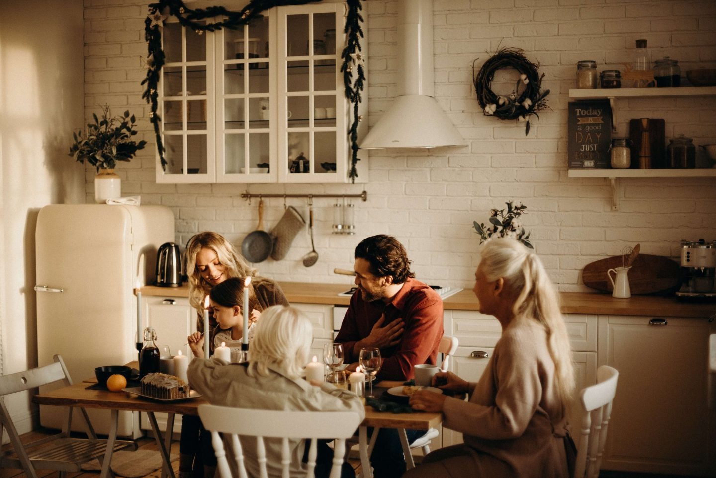 A family sat at a dining table in a kitchen enjoying food and drink