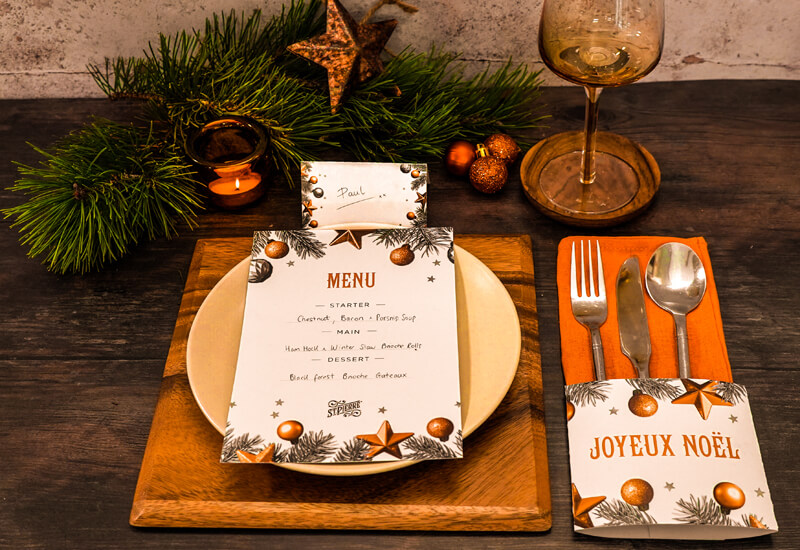 A photo of a place setting with a menu on top of a plate alongside Christmas decorations, cutlery and a wine glass