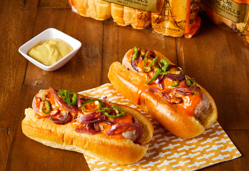 Bonfire Night recipe ideas: a photo of two hot dog rolls filled with sausages, slices of chillies and red onions and sauce