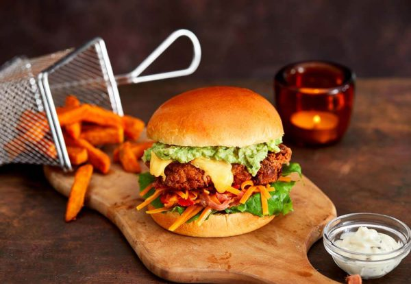 A close up photo of a burger bun filled with fried chicken, salad, melted cheese and guacamole on a wooden board with sweet potato fries