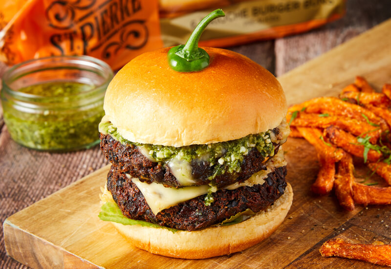 A burger bun filled with beetroot burger pucks, melted cheese and salsa verde on a wooden serving board