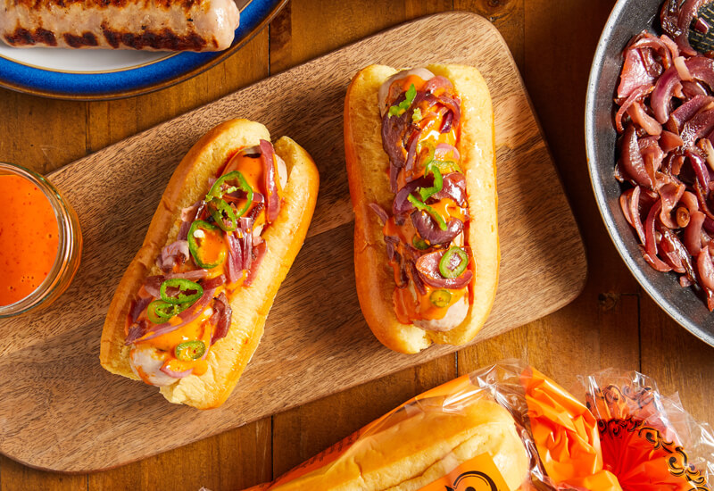 An overhead photo of brioche hot dog rolls filled with sausages, slices of chill and onions and sauce on a wooden serving board