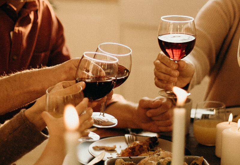A close up photo of people holding wine glasses with red wine inside