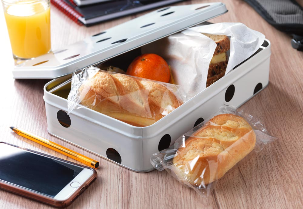 A lunch box with wrapped brioche rolls inside, as well as a sandwich and apple