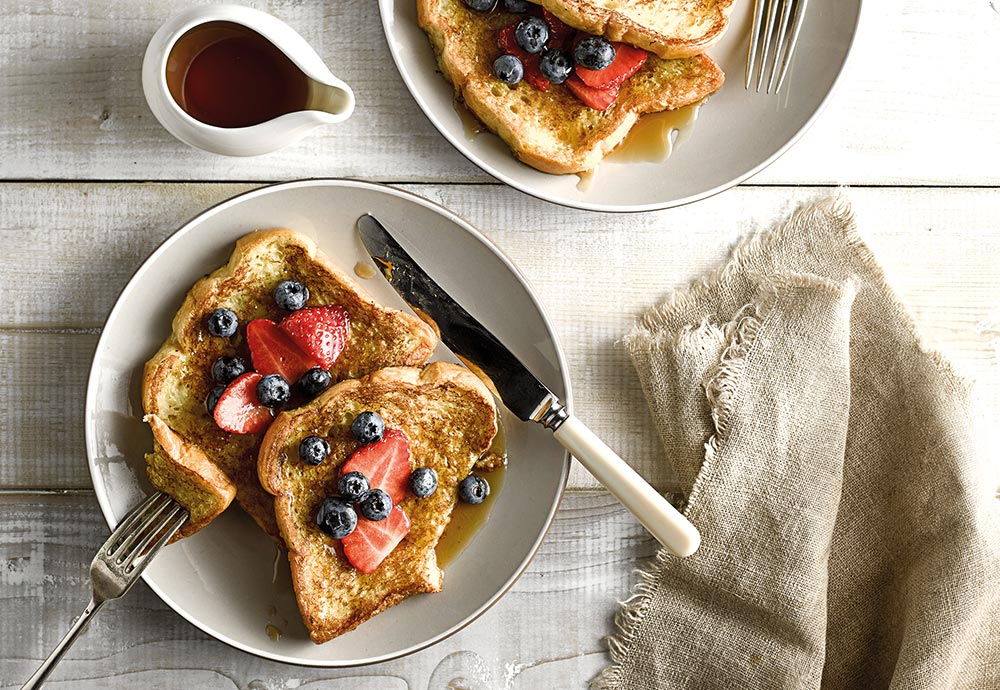 An overhead photo of a Brioche French Toast recipe on a plate with cutlery, napkin and syrup