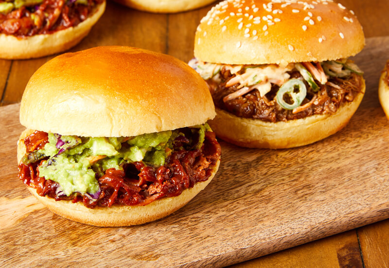 Bonfire Night recipe ideas: a close-up photo of two burgers filled with meat, avocado, guacamole and coleslaw