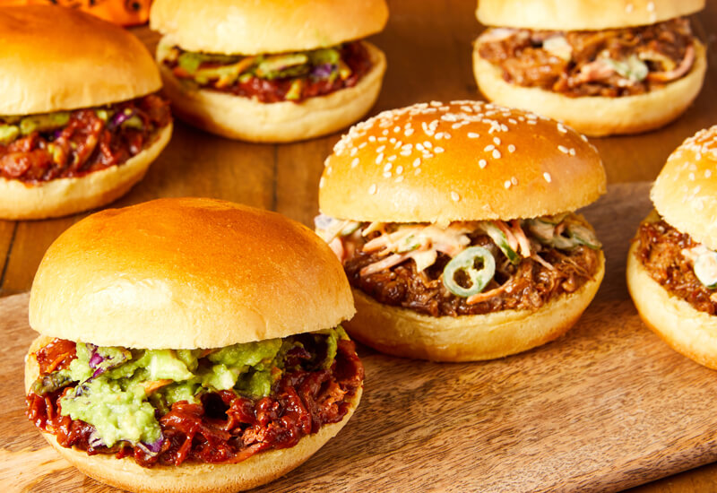 A close up of several burger buns filled with meat and toppings on a wooden serving board