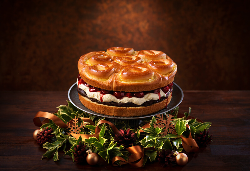 A Brioche Tear and Share sweet dessert on a cake stand filled with cherries and cream