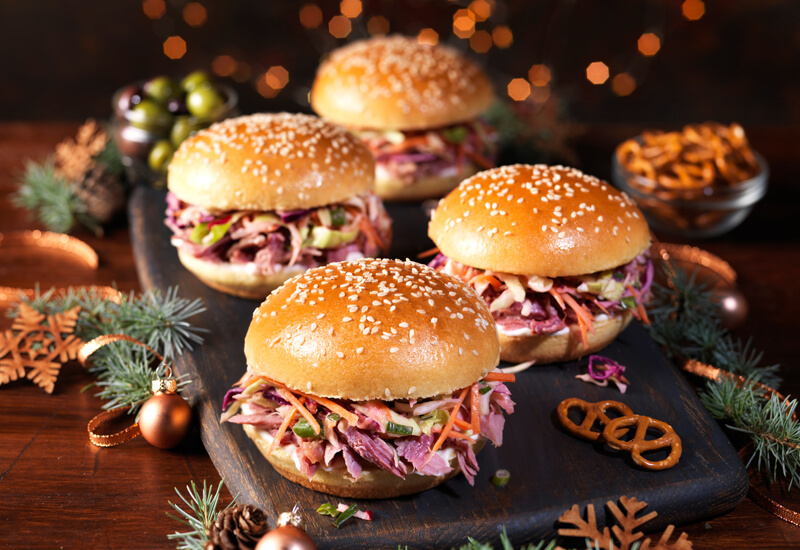 Four burgers on a wooden board with Christmas decorations surrounding them