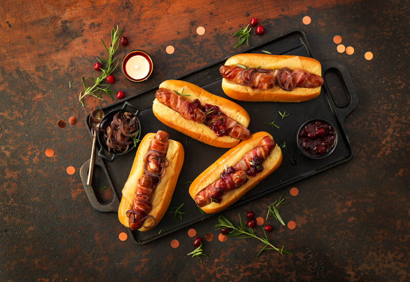 An overhead photo of pigs in blanket inside brioche hot dog rolls, topped with caramelised onions and cranberry sauce