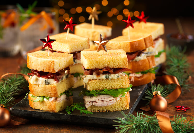 A serving board with mini stacked sandwiches on it and a stick with a star in each one