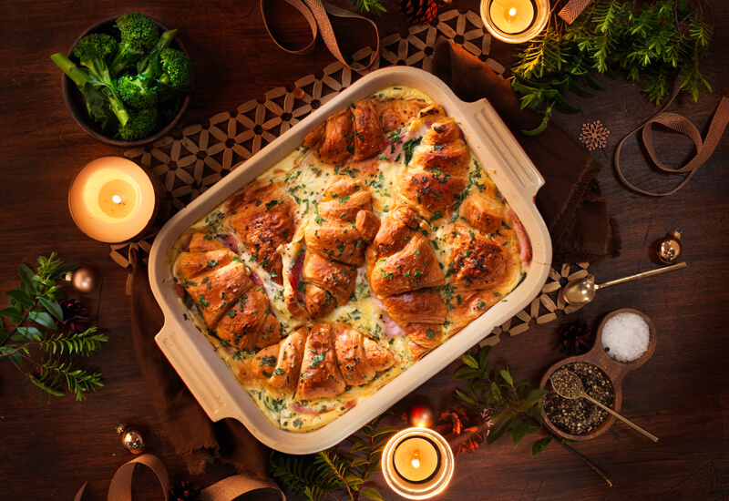 An overhead photo of a croissant savoury bake in a big serving dish surrounded by candles and Christmas decorations