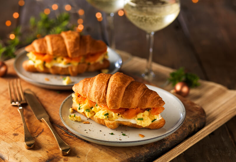 Christmas breakfast recipe ideas: two croissants on plates on a table filled with smoked salmon, scrambled egg and cream cheese