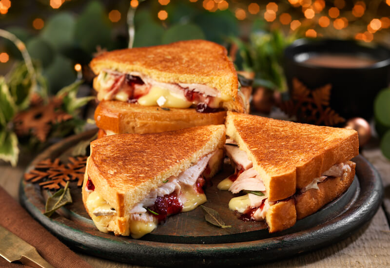Toasted turkey, cheese and cranberry sandwiches sliced in half on a wooden board