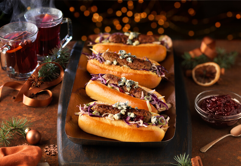Christmas food trends: four hot dog rolls on a serving dish filled with vegetarian sausages, blue cheese and red cabbage
