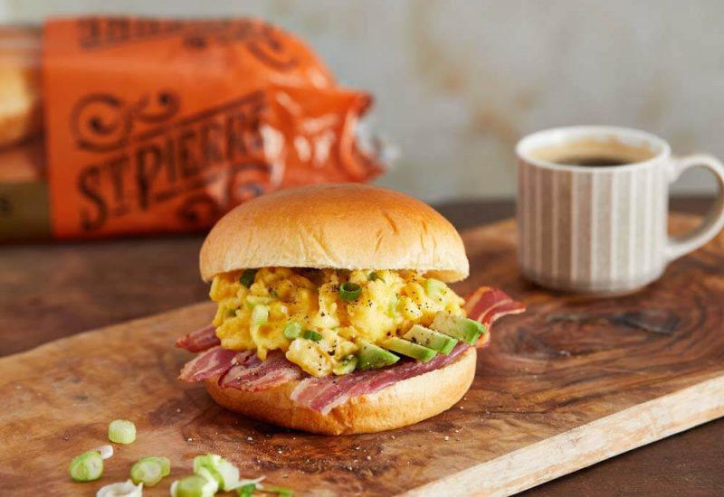 A photo of a burger bun filled with fried bacon, sliced avocado and scrambled egg on a board with a small coffee