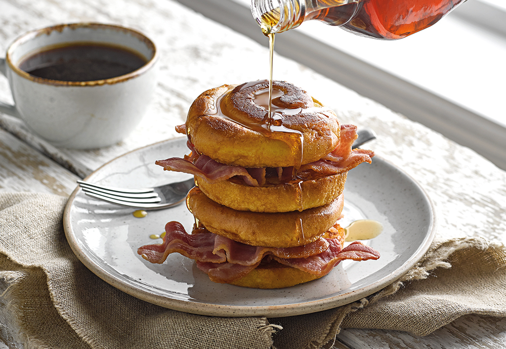 A stack of St Pierre Brioche Swirls on a plate with fried bacon in between them, and covered in maple syrup