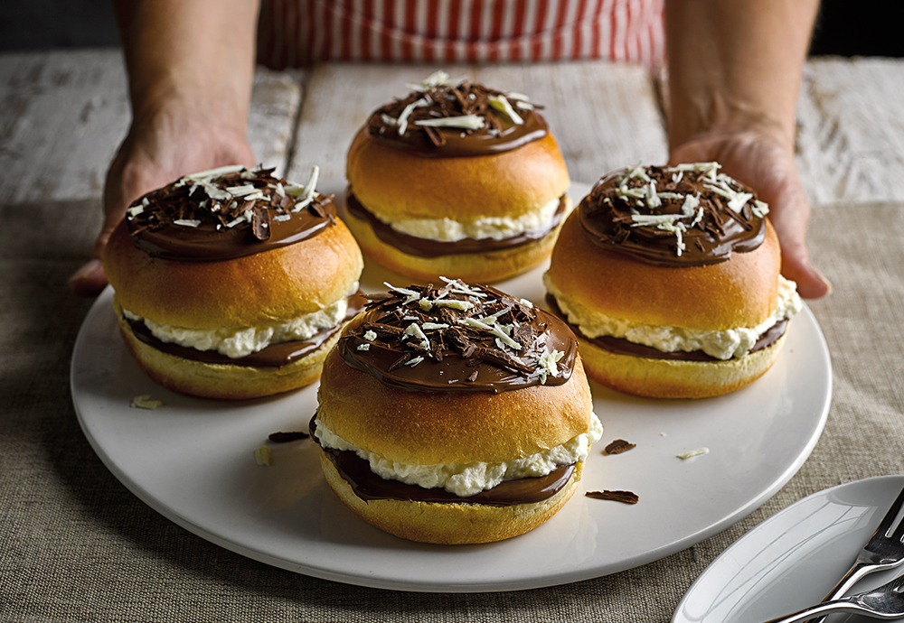 Four St Pierre Brioche Burger Buns filled with whipped cream and melted chocolate, and topped with chocolate, on a white plate