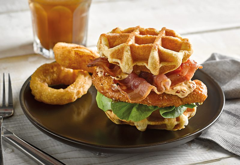 A stack of St Pierre brioche waffles on a plate, with fried bacon, lettuce and fried chicken in between them