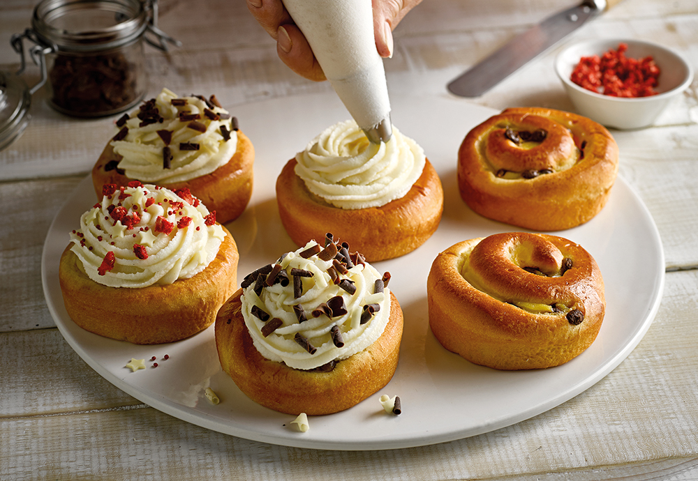 Six St Pierre Brioche Swirls on a plate with a vanilla cream frosting being piped onto one of them