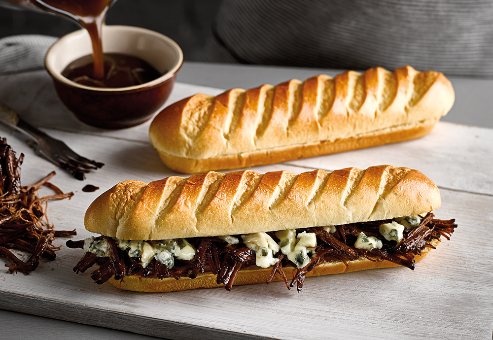Two St Pierre Soft Brioche Baguettes on a wooden board, with one filled with beef brisket and melted cheese