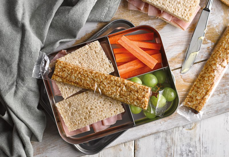 An overhead photo of a lunchbox with sandwiches, crapes and carrot sticks inside, and wrapped chocolate filled crepes on top