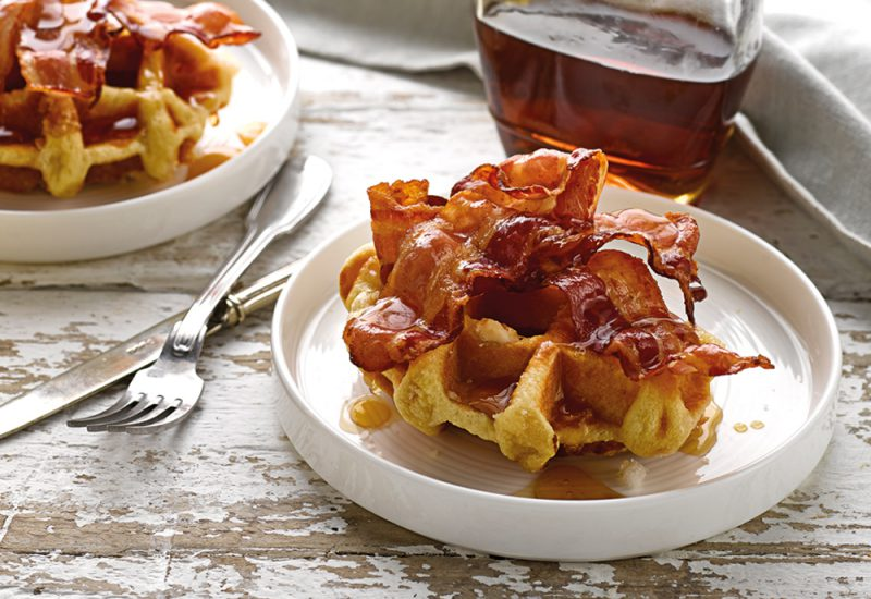 A brioche waffle on a plate with fried bacon and maple syrup on top
