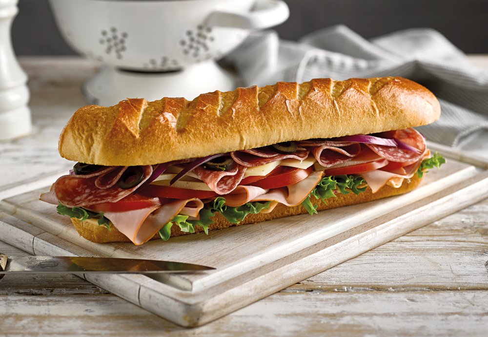 A St Pierre Soft Brioche Baguette filled with meats and salad on a wooden board with a knife next to it