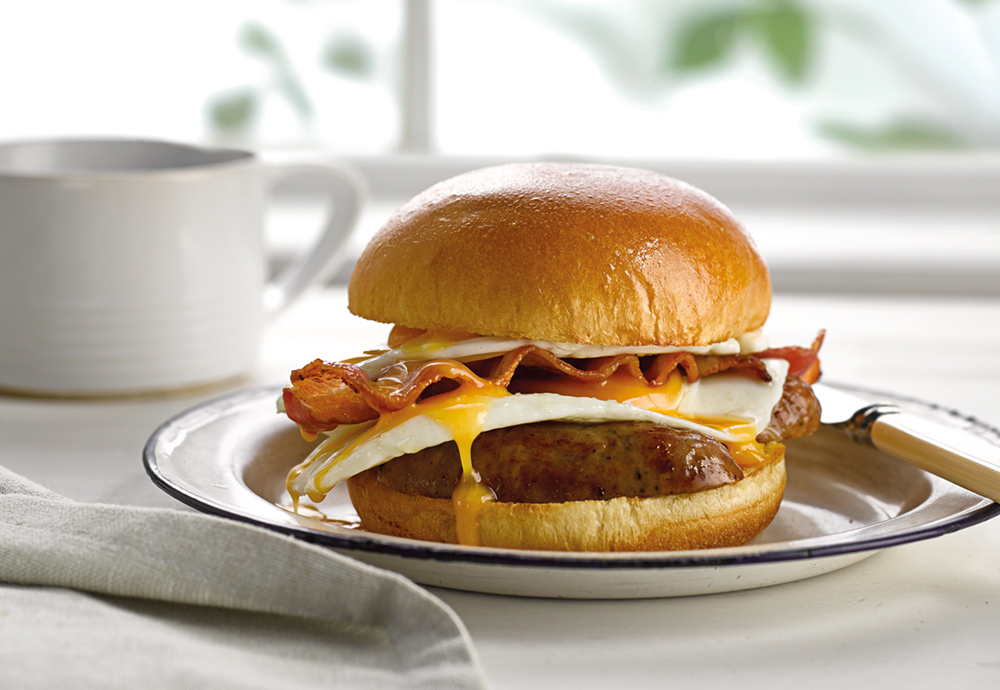 A close up of a St Pierre Brioche Burger Bun filled with sausages, fried eggs and crispy bacon on a plate with a knife on the side