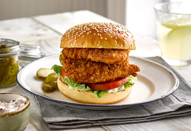 A sesame seeded brioche burger bun filled with fried chicken fillets and salad, served on a plate