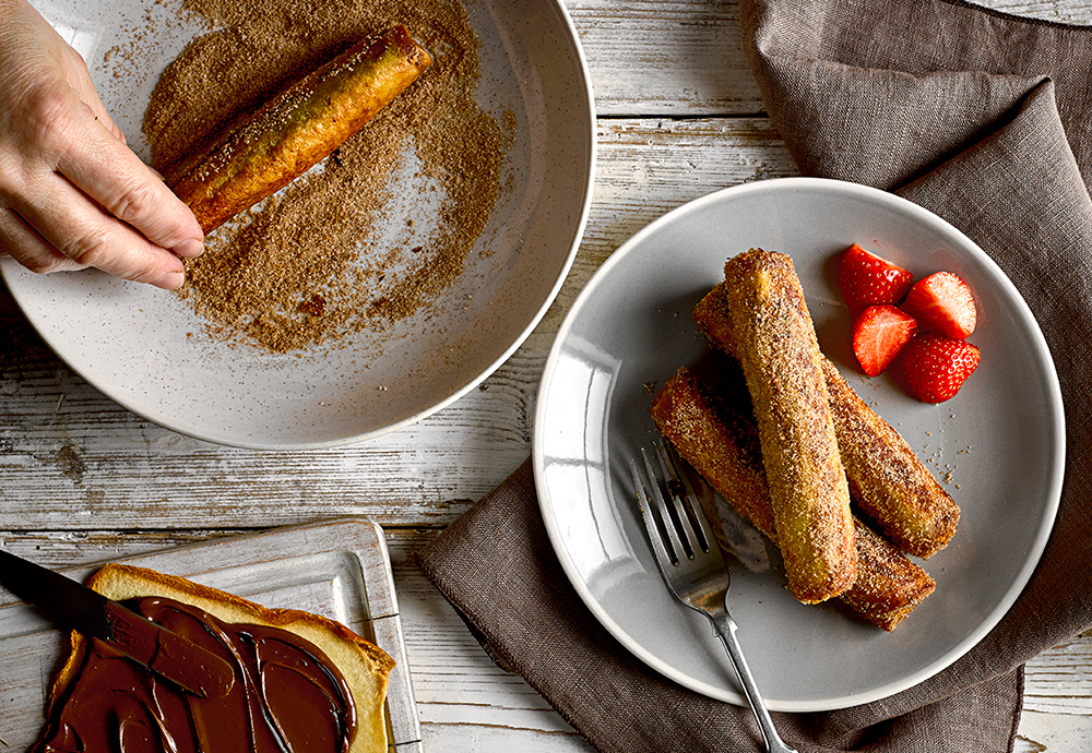 Slices of brioche loaf rolled up and dusted in a cinnamon sugar on two plates with chopped strawberries