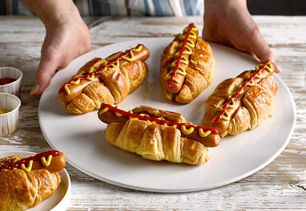 A plate of four St Pierre Brioche Hot Dog Rolls filled with sausages and topped with mustard and ketchup