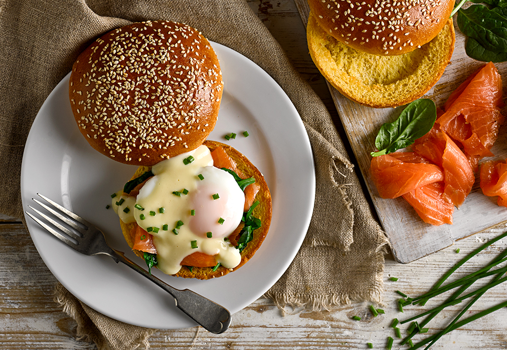 A poached egg, smoked salmon and lettuce leaves on a seeded brioche burger bun on a plate with a forkburger