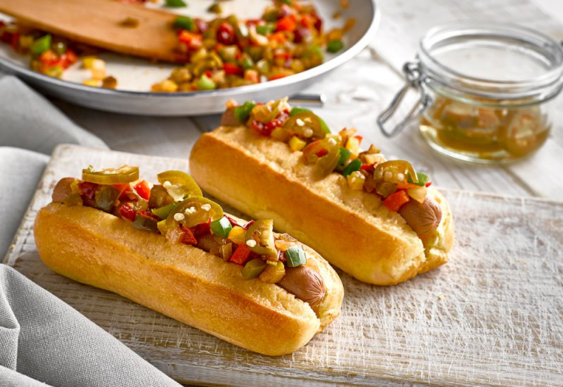 Two St Pierre Brioche Hot Dog Rolls filled with a sausage, and topped with sliced Jalapeño peppers and diced peppers