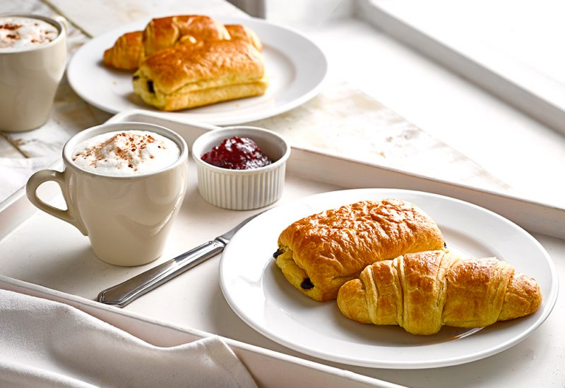 Our Classic French Breakfast recipe featuring a St Pierre Croissant and Pain au Chocolat on a table with a coffee and jam