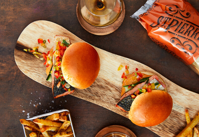 An overhead photo of two burgers on a wooden board with chips, a glass of wine and burger bun pack around the sides