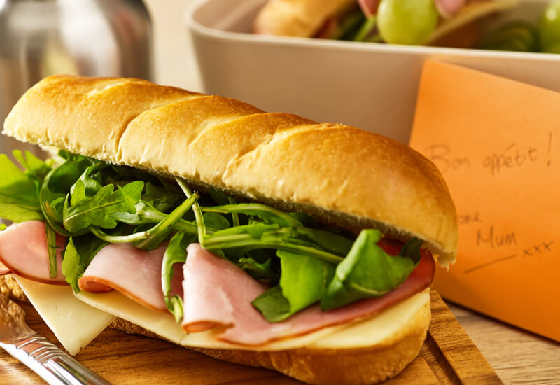 A close up of a soft brioche baguette filled with lettuce, cheese and ham next to an orange post-it note and lunch box