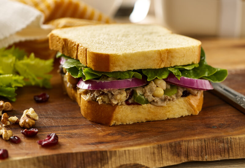 A close up of a sandwich filled with chickpeas, red onion slices and salad leaves on a wooden board
