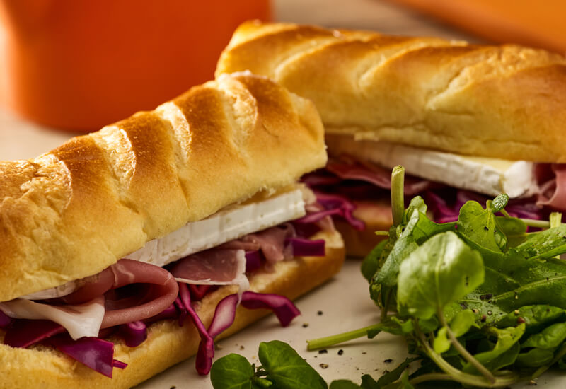 A close up of a brioche soft baguette cut in half and filled with cheese, ham and cabbage next to salad leaves