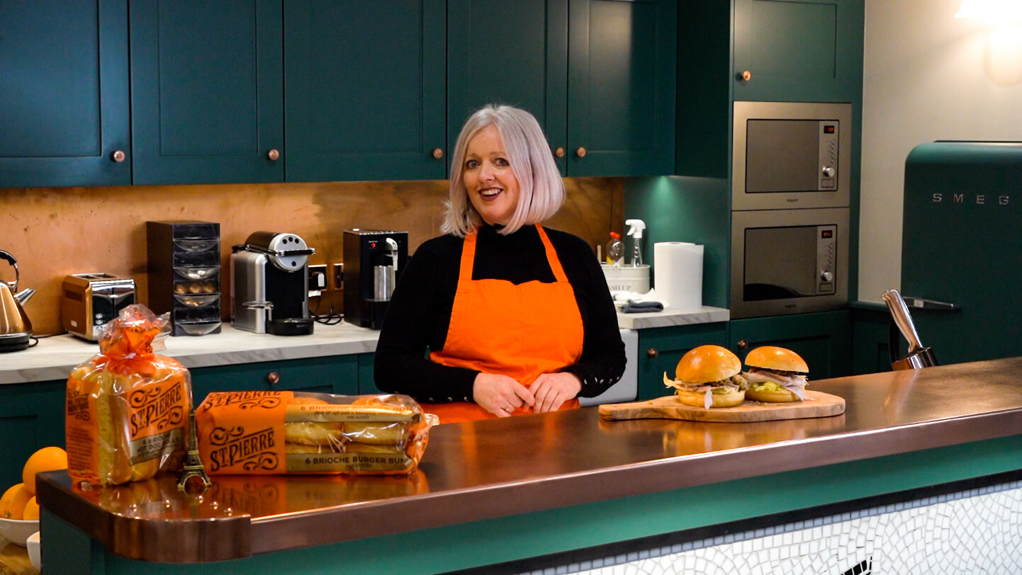 A lady in a kitchen wearing an orange apron with St Pierre products and burgers on the countertop