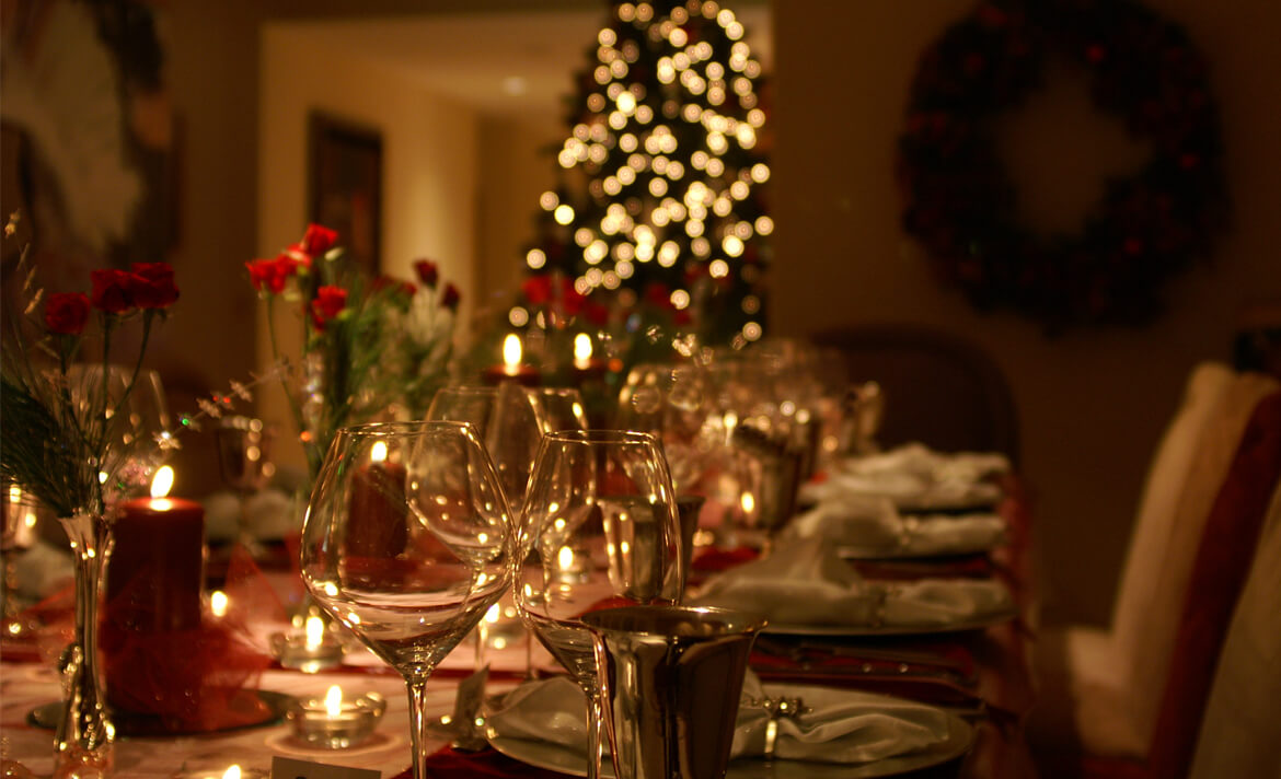 A Christmas table setting with glassware, cutlery and decorations